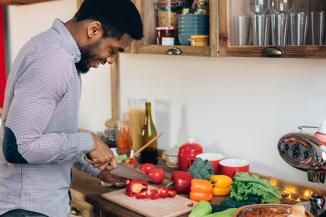 man-smiling-while-slicing-vegetables-in-kitchen