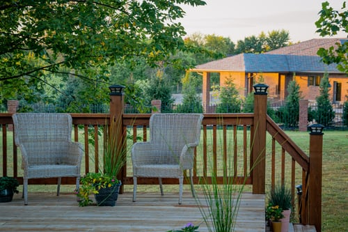 two-chairs-on-porch-near-house-in-background