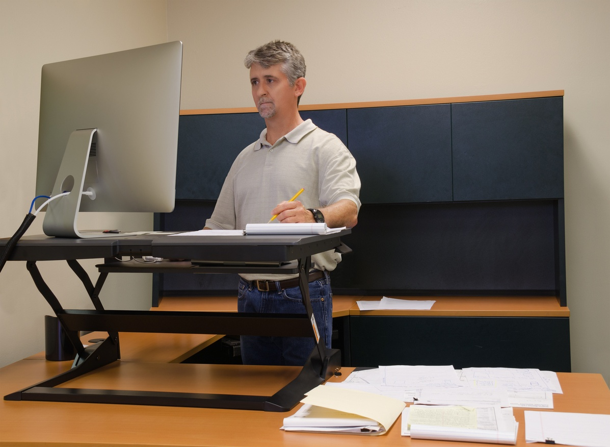 man-in-home-office-using-standing-desk-to-work-on-computer
