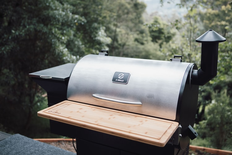 Z Grills smoker at angle in front of green vegetation