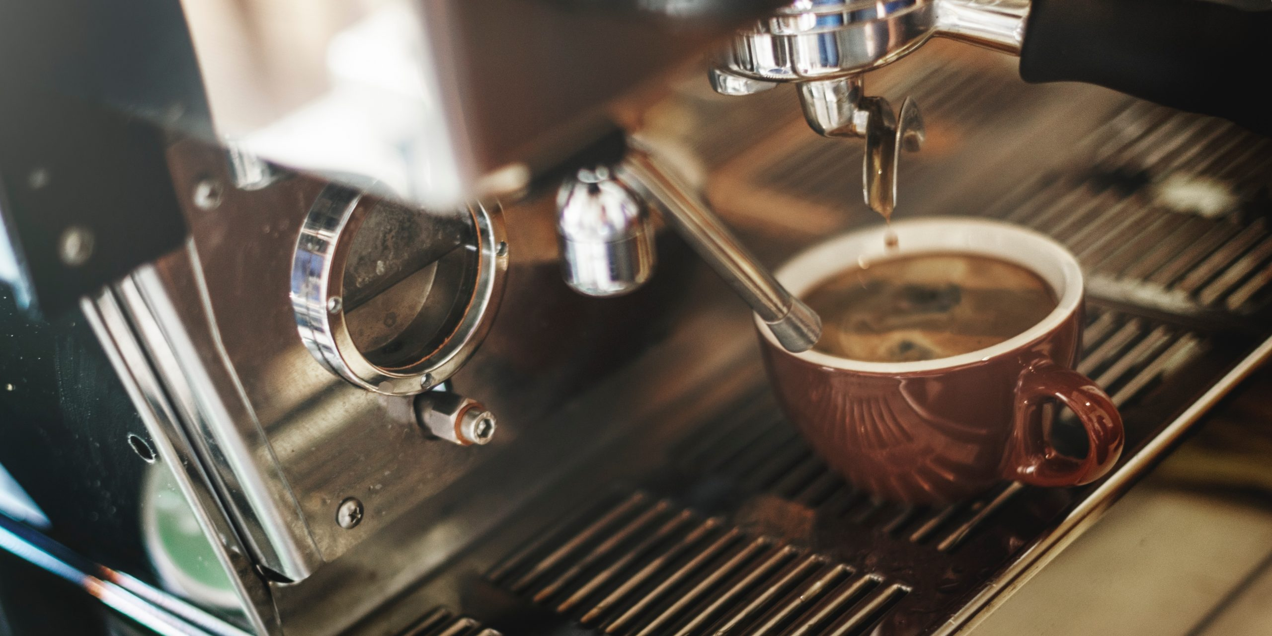 close-up-of-espresso-machine-with-cup-filled-with-coffee