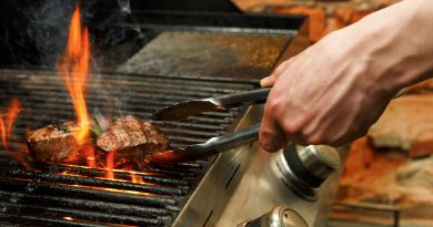 hand using tongs to flip steaks on a grill with flames