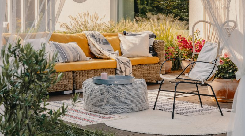 modern-outdoor-furniture-set-including-wicker-sofa-with-yellow-cushions-and-metal-chair