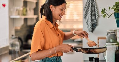 smiling-woman-in-profil-standing-in-kitchen-and-stirring-pan-with-spatula-while-meal-prepping