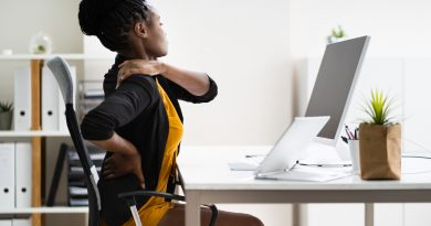 woman-massaging-sore-shoulder-while-sitting-at-desk-in-home-office