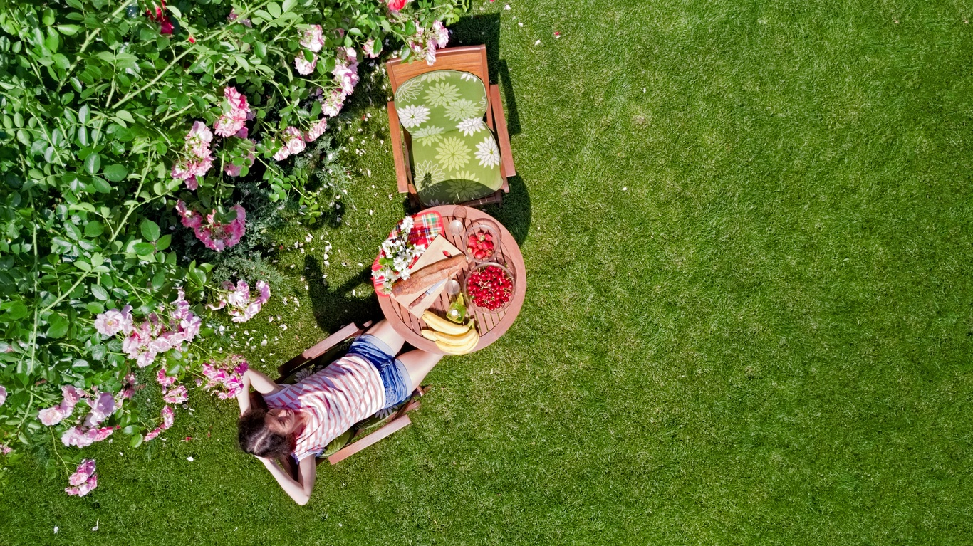 bird's-eye-view-of-woman-sitting-in-chair-at-circular-table-on-lawn-with-meal-and-empty-second-chair