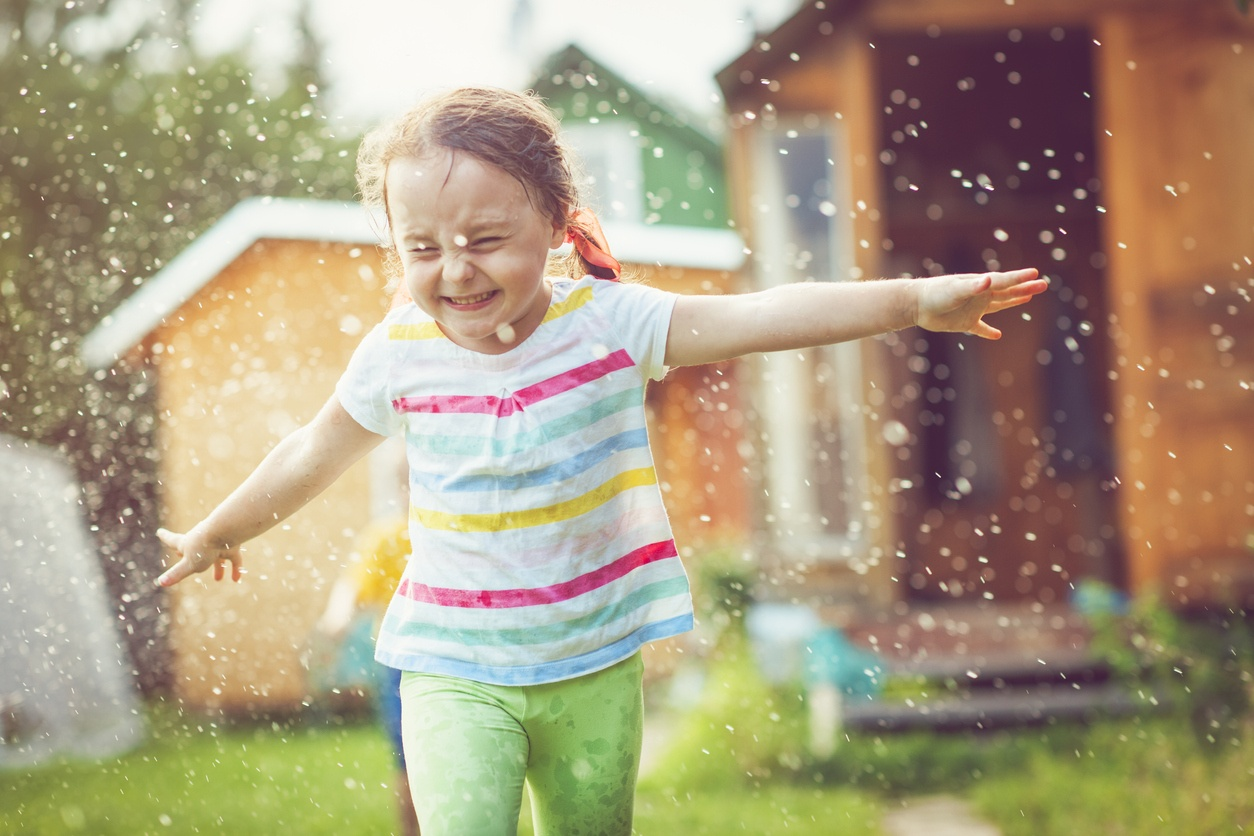 little-girl-in-striped-shirt-and-green-pants-running-through-sprinkler-with-arms-stretched-out-sideways