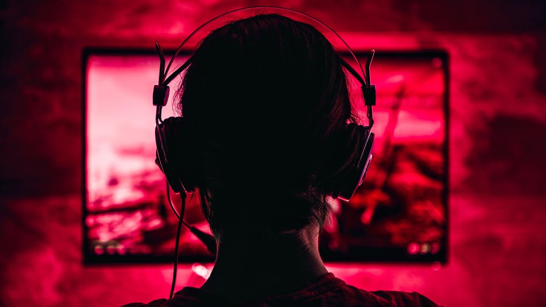 gamer-facing-away-from-camera-towards-red-lit-screen