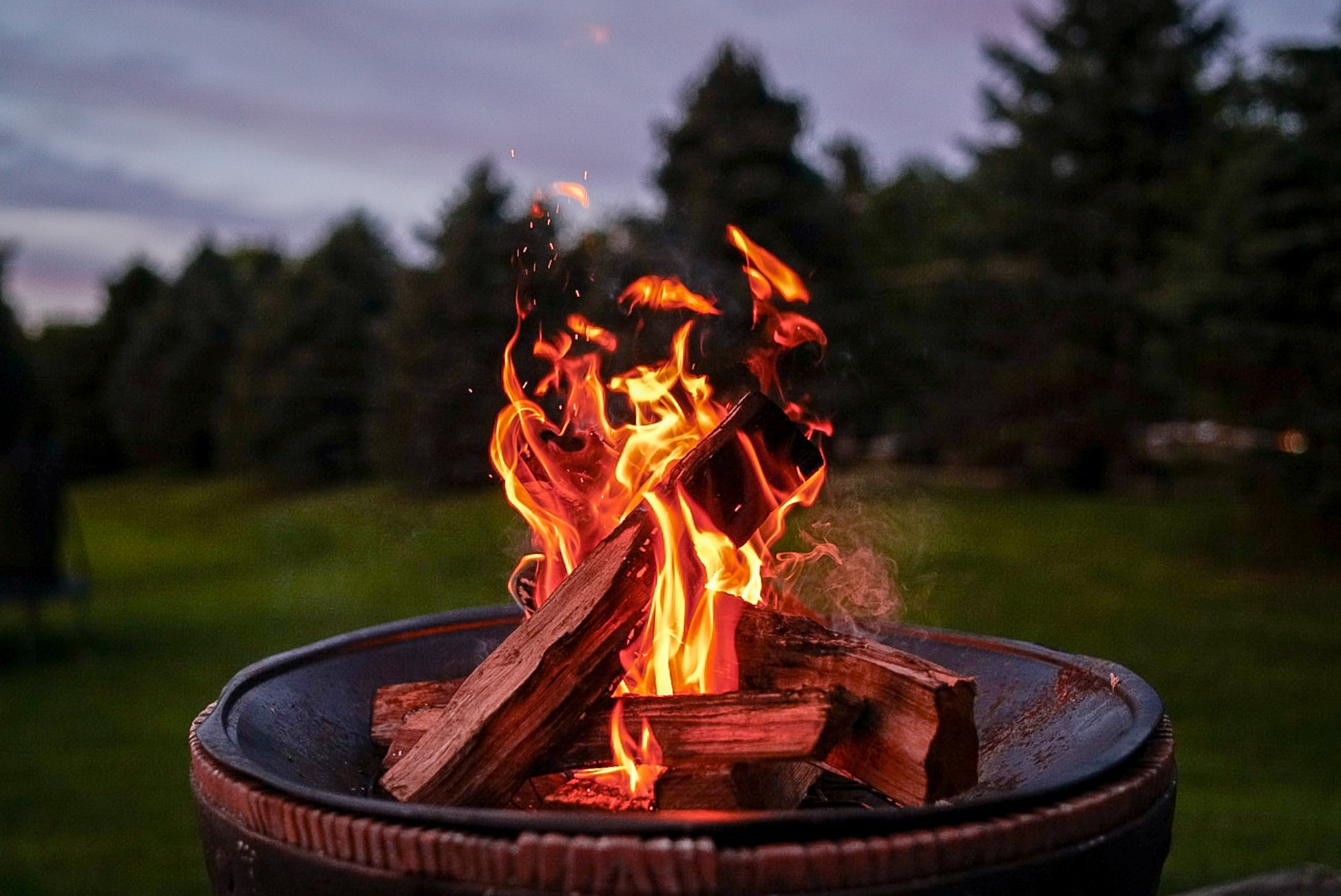 wood-burning-fire-pit-with-flames-and-green-trees-in-background