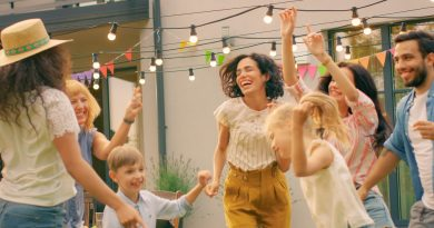 adults-and-children-dancing-in-backyard-listening-to-music-from-outdoor-speakers-under-string-lights