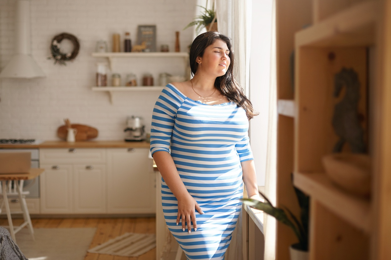 woman-in-blue-and-white-half-sleeve-dress-standing-by-window-in-living-room