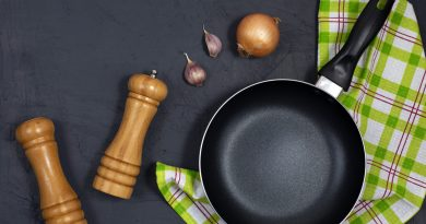 flat-lay-with-nonstick-pan-teflon-on-green-checkered-towel-with-pepper-grinders-onion-and-garlic-cloves-nearby-on-dark-surface