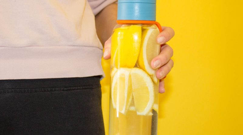 cropped-photo-of-woman-holding-glass-water-bottle-with-lemons-inside-against-yellow-background