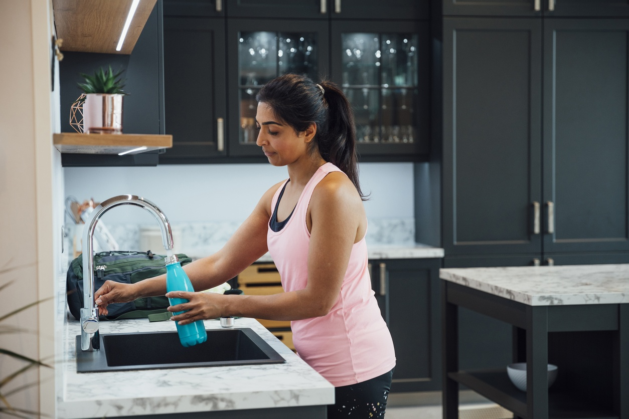 woman-wearing-workout-clothes-filling-tapered-water-bottle-at-kitchen-sink-with-black-cabinets-in-background