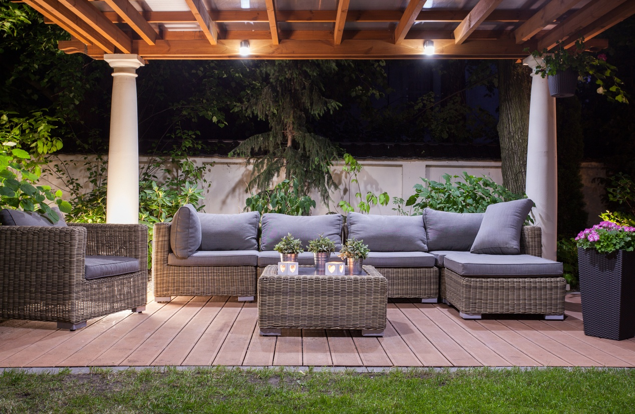 faux-wicker-patio-furniture-set-with-grey-cushions-under-canopy-at-night