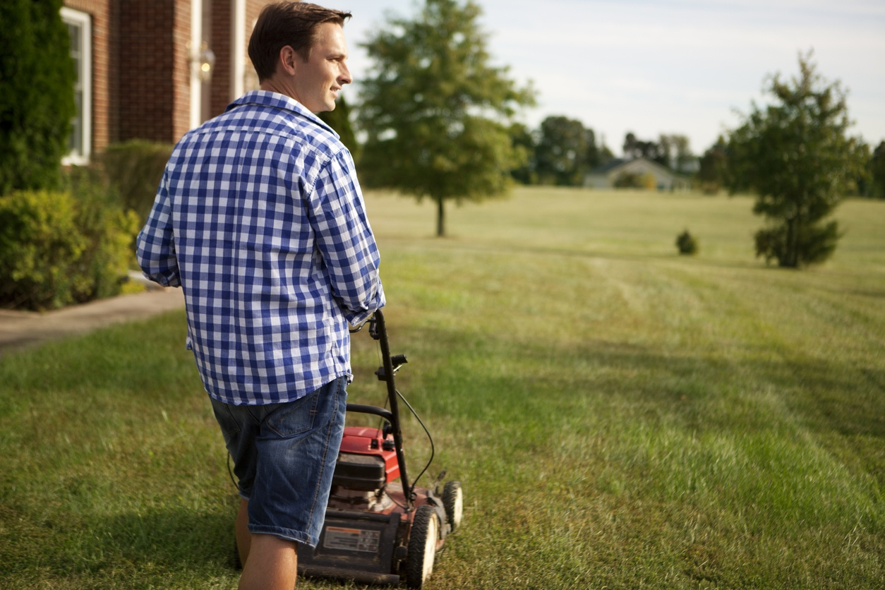 man-wearing-checkered-shirt-and-shorts-pushing-lawn-mower-on-grass-next-to-house-and-trees