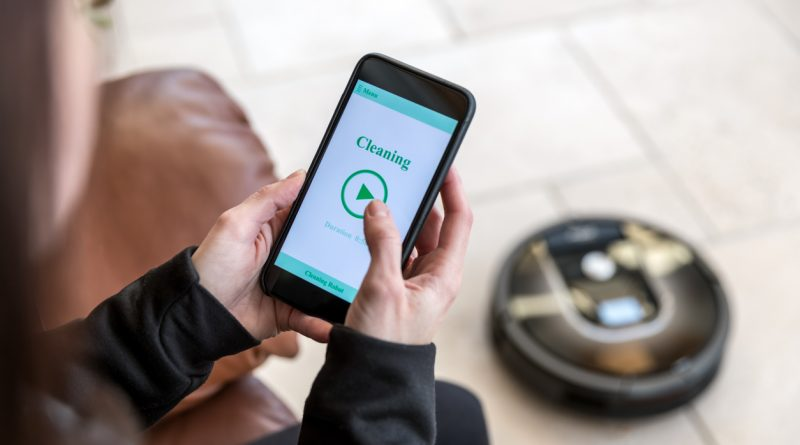 woman-holding-smartphone-robot-vacuum-app-on-cleaning-mode-with-robot-vacuum-on-floor-in-background