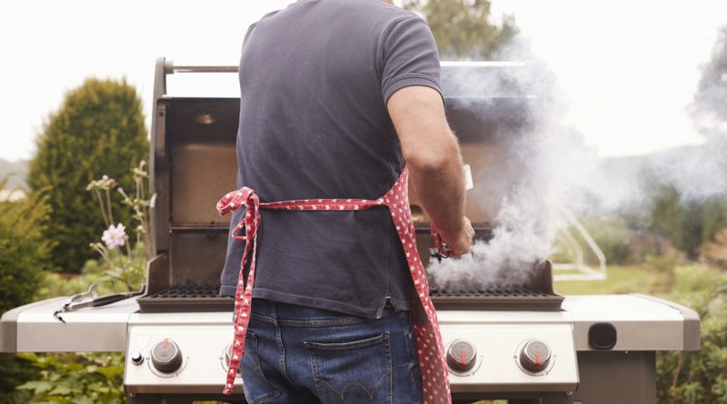 man-facing-away-from-camera-standing-at-gas-grill-cooking-food