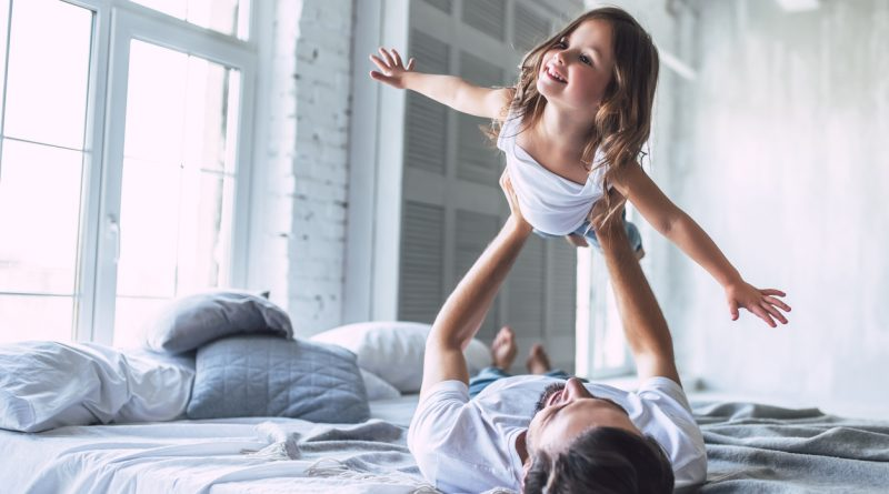 man-laying-on-back-on-bed-while-holding-young-daughter-aloft-like-airplane