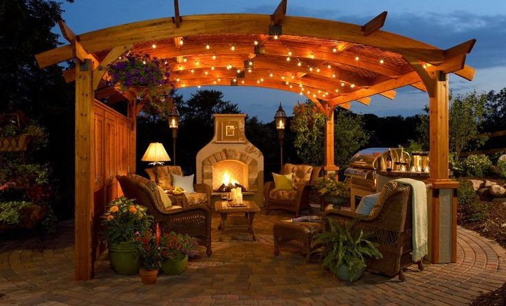A backyard patio with mosquito repellents under a wooden structure lit by fairy lights and a wood fire stove