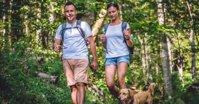 A man and a woman hiking through a forest with a small brown dog