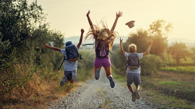 Three kids jumping into the air with their arms up while hiking on a gravel path and wearing camping and hiking backpacks