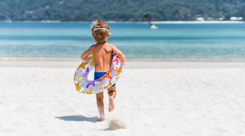 A young boy wearing blue swim trunks is running with an inner tube around his waist on a beach towards the water