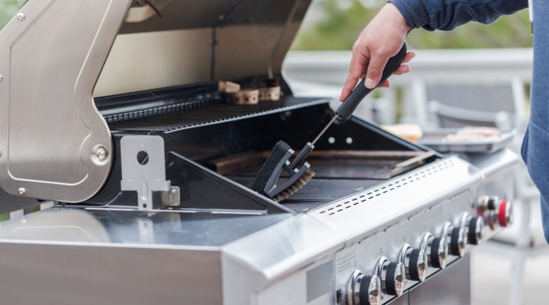 A person's arm scraping a gas grill grate with a grill brush.