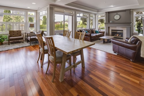A wooden dining table and chairs in an open-concept kitchen and living room area.