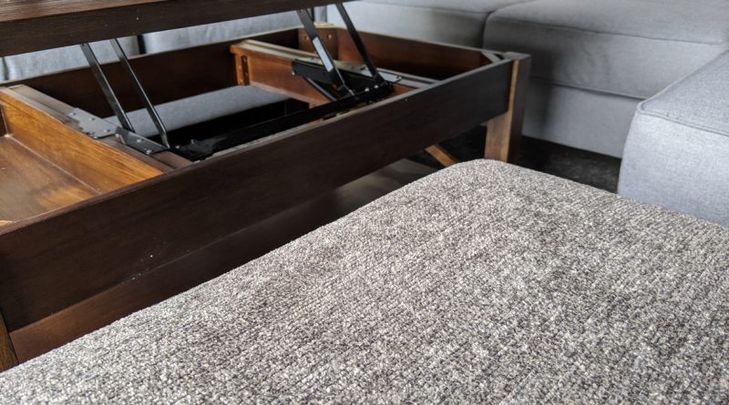 A lift-top-coffee table with the top extended near an L-shaped grey couch.