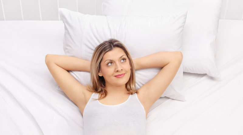A woman laying on a bed with white sheets with her head on two pillows and her hands behind her head.