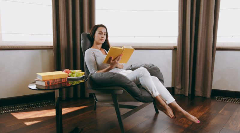 A woman sitting in a reading chair with a high back and low armrests while reading a book with a yellow cover.