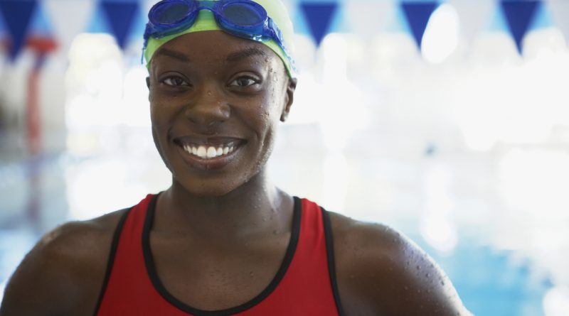 An African American woman wearing a lime green swim cap and a red swim suit smiling at the pool.