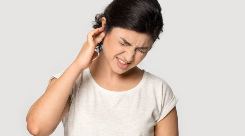 Young woman holding her right ear in pain and grimacing.