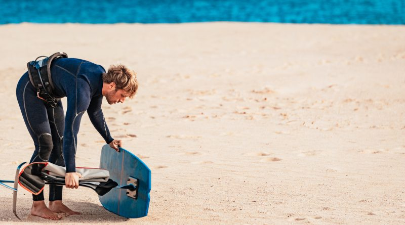 A man in a wetsuit bending down to adjust a hydrofoil wakeboard on a beach.