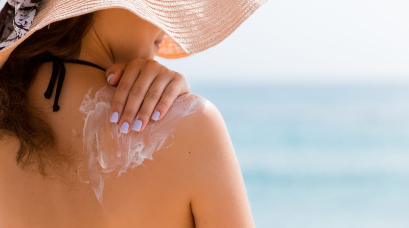 A woman wearing a sun hat and a bathing suit applying sunscreen to her shoulder on the beach.