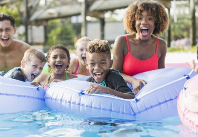 A group of kids with two adults in a lazy river at a water park with inner tubes.