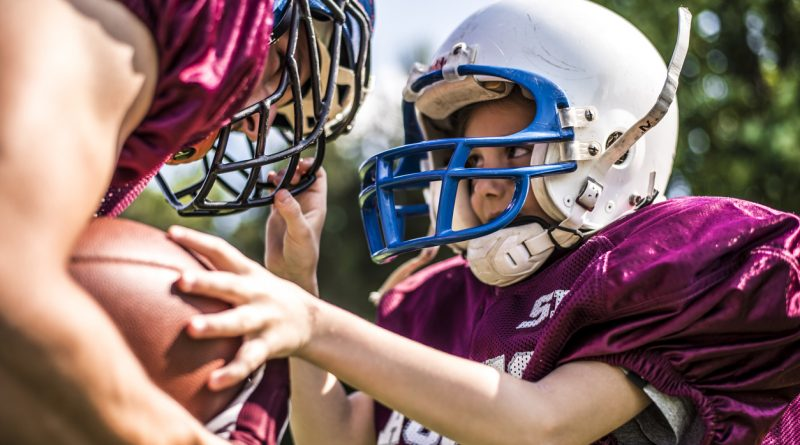 Young football player wearing a youth football helmet while training with her coach.